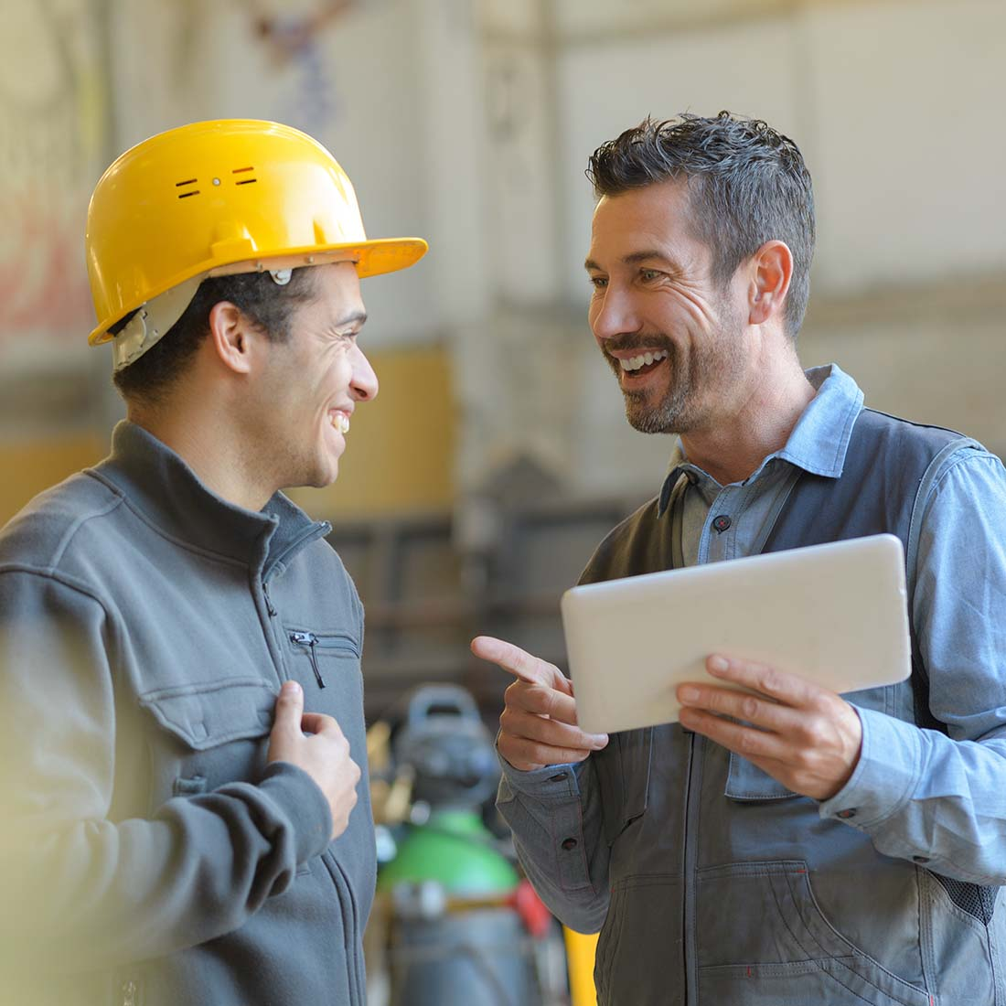 Male factory worker talking and smiling with supervisor