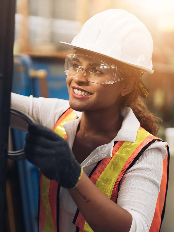Female factory worker inspecting equipment and smiling